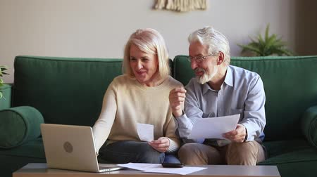 factuur : Smiling aged married couple sitting manage family budget check receipts loan contract conditions use e-banking, older generation online services modern tech easy usage, accounting, bookkeeping concept