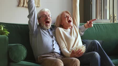 ağarmış : Excited sixty years spouses old hoary couple sitting on couch in living room eat popcorn cheer supporting for favourite football team raising hand screaming with joy celebrating success victory moment