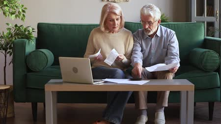 makbuz : Stressed elderly spouses couple sit on couch in living room managing family budget checking expenses feels anxiety worried about overdue, high taxes, lack deficit of money accounting problems concept Stok Video