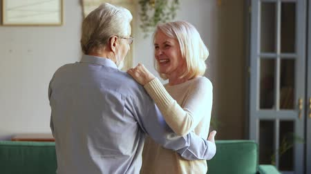 ağarmış : Elderly spouses having pleasant conversation share memories during waltz dancing, hoary husband in glasses hugs the waist holds hands of beloved wife chatting enjoy life active weekend at home concept Stok Video
