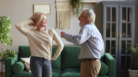 ağarmış : Elderly spouses standing in living room listening energetic music dancing together, senior hoary rock-n-roll dancers enjoy life feels happy and healthy spending active free time on weekend at home Stok Video