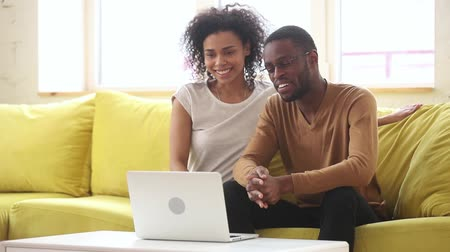 parentes : African married couple sit on yellow couch looking at pc screen webcam wave hands greeting friends relatives distantly talking telling about cold weather have fun use video conference tech app concept