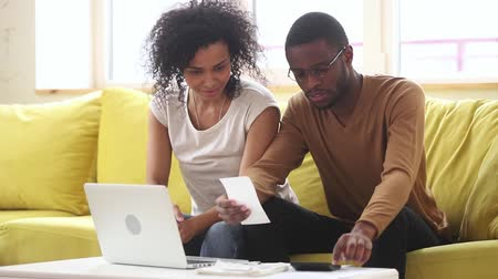 makbuz : African millennial couple sitting on couch managing family budget summarize checks and costs using calculator and online application on laptop, try achieve financial success, money management concept