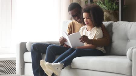výhoda : Black father hugs little daughter sitting together on couch in living room loving daddy reading book fairy tale interesting story spend free time to good advantage, upbringing education of kid concept Dostupné videozáznamy