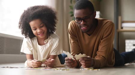 develop : Black father and daughter lying on warm heated floor having fun assembling jigsaw puzzle putting connecting pieces. Hobby leisure activity, logical reasoning and development of solving skills concept Stock Footage