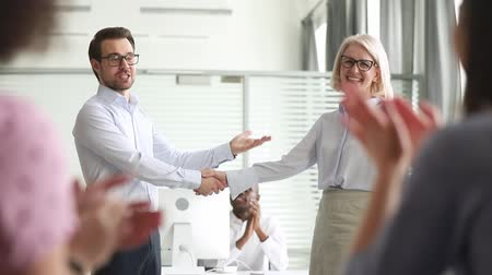 övgü : Corporate members clap hands applauding cheering looking at company boss shaking hands aged woman express gratitude for successful work done employee of month or congratulating with retirement concept