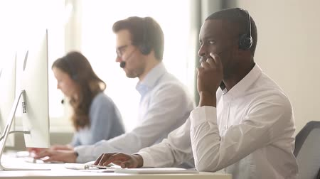 yardım hattı : Call center diverse employees working in shared desk focus on african worker wearing headset typing look at pc screen talk help to company client distantly, provide information helpline office concept