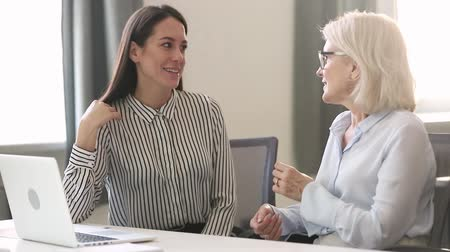 informal : Different generations european businesswomen sitting together at desk discuss business issues, middle aged and young office workers having friendly conversation, mentor intern planning shared project Stock Footage