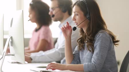 complaints : Service phone operators sit at shared desk focus on sales agent woman in headset use pc answers incoming calls talk with client provide professional support to customers sell company product concept Stock Footage