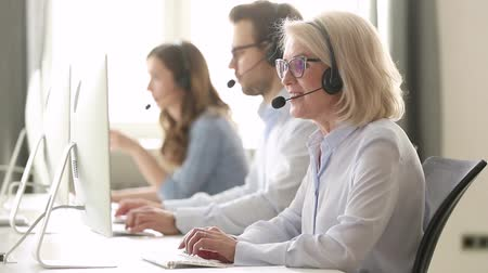телемаркетинг : Aged woman call center employee sitting at workplace having busy workday, sales agent wearing headset use computer typing search information provide help to client distantly helpline office concept