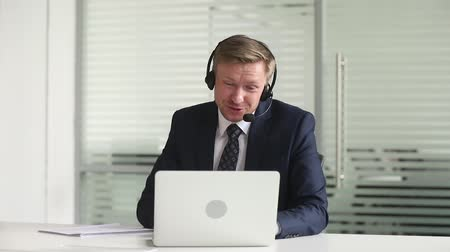 телемаркетинг : Businessman sitting at desk wearing headphones with microphone having productive teleconference talking with corporate client using computer web camera negotiations distantly modern tech usage concept Стоковые видеозаписи