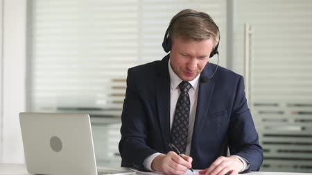 discussion meeting : Businessman sitting at desk in office wearing headset using microphone talks negotiating with company client makes notes, videoconferencing make deal solve business issues online via internet concept