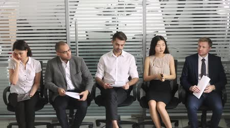 candidato : Different ethnicity multi-ethnic businesspeople sit in chair in queue waiting job interview feels stressed and nervous, competition company position vacancy. Human resources, recruiting agency concept