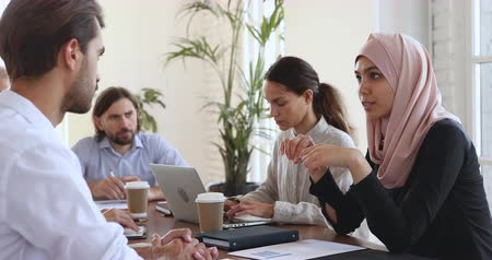 muslim leader : Asian muslim female manager consulting caucasian male partner at group office meeting table, islamic ethnic businesswoman make business offer speak to client explain corporate project at negotiation Stock Footage