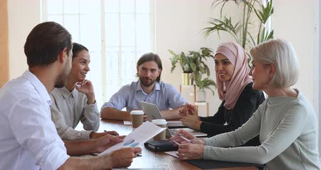 muslim leader : Caucasian businessman speaking to multicultural business people consulting clients at meeting table, male manager negotiating with diverse customers team work group during contract negotiations