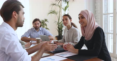 peça : Asian muslim female client wear hijab ask question speak to partner discuss project contract at diverse group negotiation, multicultural business people negotiating planning strategy at meeting table
