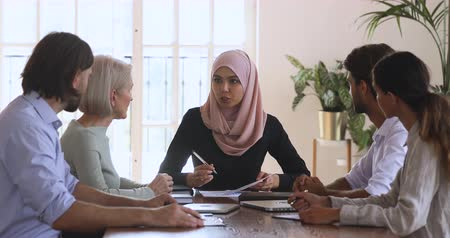 multikulturális : Young asian muslim female company leader discuss paperwork at team meeting, islamic businesswoman executive wear hijab review financial results consult employees group at corporate briefing table