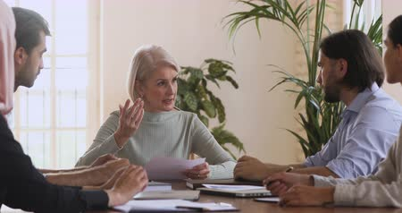 brifing : Serious confident middle aged older female leader mentor boss holding papers talking to team staff people discussing new marketing plan or financial result paperwork at group corporate briefing table Stok Video