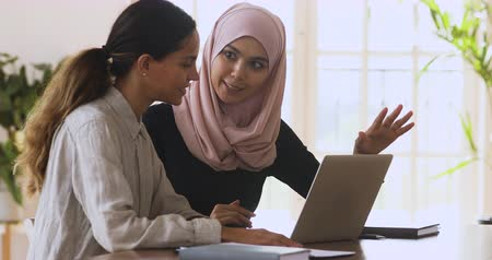 muslim leader : Female asian muslim manager mentor wear hijab consult caucasian client teaching intern trainee with laptop talk in office, two diverse ethnic businesswomen discuss online work at corporate meeting