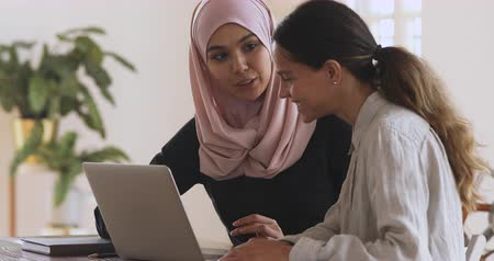muslim leader : Friendly asian muslim female mentor teacher help young caucasian intern trainee teach new worker apprenticeship course learn new skills explaining computer software work at modern workplace concept