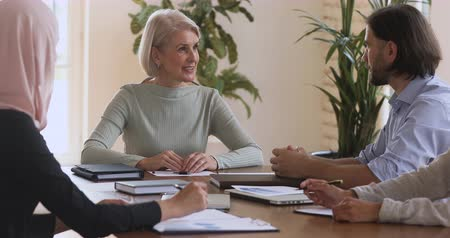 uznání : Happy mature older female company leader manager handshake male partner at team meeting promoting employee making business deal agreement with client at group negotiations sitting at conference table. Dostupné videozáznamy