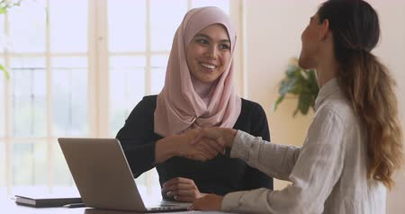 dankbaarheid : Happy female asian muslim insurer mentor sales manager shake hand of caucasian client customer intern coworker thank for help make business deal agreement at office corporate meeting with laptop.