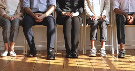 vaga : Professional unemployed jobless business people group waiting for job interview, male female seekers sit on chairs in row line queue legs close up view, human resources and employment concept