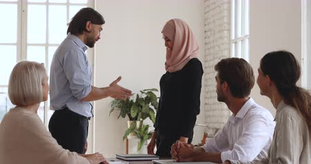 reconhecimento : Caucasian male boss handshake promote praise successful female asian muslim worker wear hijab get good feedback applause at meeting, gender equality, employee recognition and office reward concept