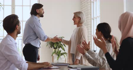 juntar : Happy older mature female company employee get promoted rewarded handshaking boss admiring praising appreciating successful middle aged worker give good feedback team applause recognition concept