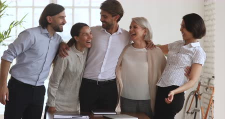 motive : Overjoyed excited multiethnic young and old business people friendly team embrace bonding laugh celebrate corporate success, professional achievement victory triumph at staff office party concept