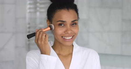mindennapi : Smiling young attractive african woman wear gown hold brush apply powder on face healthy skin put cosmetics looking at camera, happy confident mixed race girl doing morning beauty makeup in bathroom