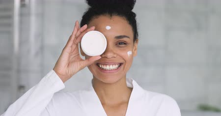 teen age : Happy beautiful african young woman apply cream on face laugh looking at camera holding creme jar in bathroom pointing aside advertise facial skin care moisture treatment hydration, skincare concept Stock Footage
