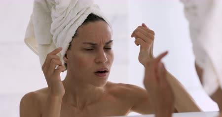пятна : Shocked upset young lady with towel on head look in mirror feel stressed about facial skin problem, worried depressed girl touch face frustrated annoyed by blackhead acne pimple in morning bathroom