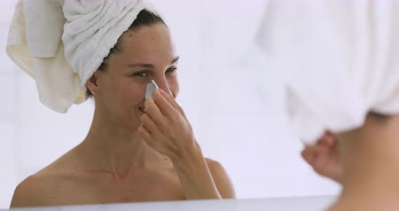 puberteit : Happy attractive young woman with towel on head remove nose strip looking in mirror in bathroom, smiling teenage girl cleansing face pores blackheads, healthy clean skin care treatment concept