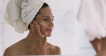 tonik : Smiling healthy young woman with towel on head apply facial creme look in mirror, happy lady put cream on face do morning makeup beauty routine in bathroom enjoy moisturized skin, skincare concept