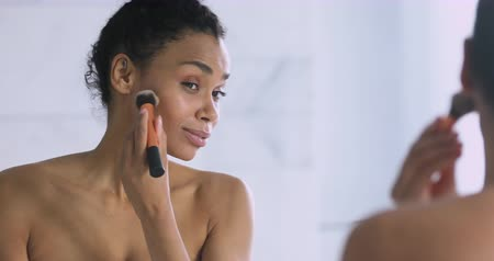 mindennapi : Happy beautiful young african woman applying powder on face healthy flawless skin holding brush, smiling pretty mixed race girl doing makeup put cosmetics looking in mirror in the morning in bathroom
