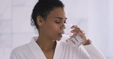 hidratar : Beautiful young healthy african woman wear gown holding glass drinking fresh mineral water in morning, thirsty mixed race girl feel thirst keep hydration diet nutrition weight loss balance concept Stock Footage