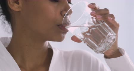 bodywarmer : Thirsty young african woman holding glass drinking fresh mineral pure clean water, healthy lady hydrating thirst in the morning keep hydration balance for skin body healthcare concept, close up view
