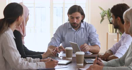 multikulturális : Confident male ceo leading corporate staff meeting sit at table, businessman boss leader speaking to diverse employees team at multicultural group briefing explaining project planning work in office Stock mozgókép