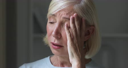 luto : Sad depressed miserable mature older adult woman crying mourning, upset stressed middle aged lady in tears alone at home think of loneliness upset about solitude suffering from grief sorrow concept Stock Footage