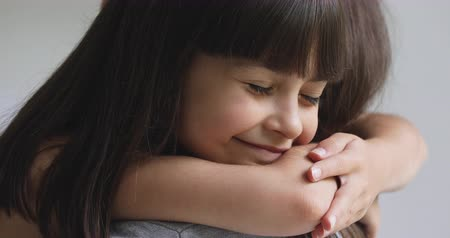 foster : Happy cute affectionate adopted little kid girl hugging foster care parent mother with eyes closed, adorable small child daughter embrace mum cuddling enjoy tender sweet moment concept, close up view Stock Footage