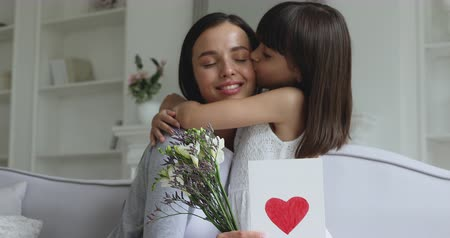 agradecido : Loving cute small kid child daughter hugging kissing happy young mum congratulating with mothers day concept embracing grateful mommy holding spring flowers and greeting card with red heart at home Archivo de Video