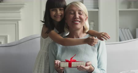 agradecido : Happy cute little child granddaughter embracing kissing old middle aged grandma foster care parent presenting gift box making surprise congratulating with birthday holiday hugging having fun at home