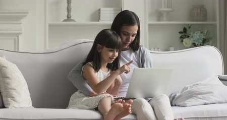 conferencing : Happy parent young mum and cute little child kid daughter looking at laptop screen choosing buying holiday presents in online shop together having fun using notebook at home relax talk sit on sofa