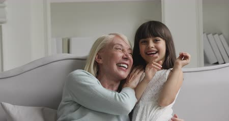 nanny : Happy family mature old grandma and little cute girl granddaughter enjoy play game tickle laugh at home, cheerful middle aged grandparent having fun with small grandkid relax on sofa cuddle together
