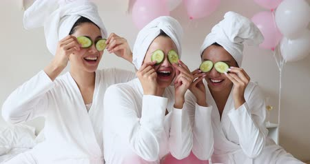 pajama : Funny happy young asian women friends wear white dressing gowns towels on head make cucumber facial skin care mask on eyes laugh having together look at camera on spa beauty salon party with balloons