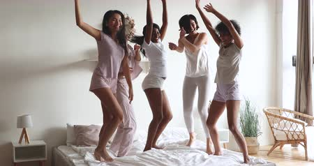 nachtkleding : Crazy funky beautiful diverse young girls best friends dancing having fun stand on bed, funny sexy multiracial ladies group wear pyjamas jumping in bedroom together enjoy slumber pajama party concept