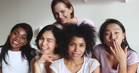 yatak kıyafeti : Smiling pretty multicultural young girls best friends wear pyjamas bonding laugh look at camera, five happy carefree multiracial playful ladies gather on slumber party, multiethnic friendship concept Stok Video