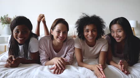 nachtkleding : Four smiling happy multiracial beautiful young women diverse best friends students wear pyjamas lying on bed looking at camera together gather at sleepover pajama slumber party concept, portrait