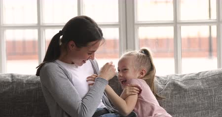 nanny : Cheerful young adult mum tickling small kid daughter playing together sitting on sofa, funny happy family cute little child girl having fun with mother enjoy lifestyle game embracing laughing at home